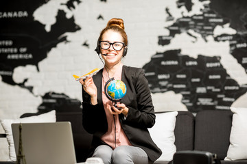 Portrait of a female travel agent in suit and headset playing with globe and airplane on the world map background