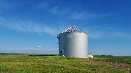 Metal silo on farmland in rural landscape