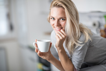 Beautiful blond  caucasian woman posing in her kitchen, while drinking coffee or tea and eating a healthy breakfast meal full of cereal and other healthy foods, including fruit