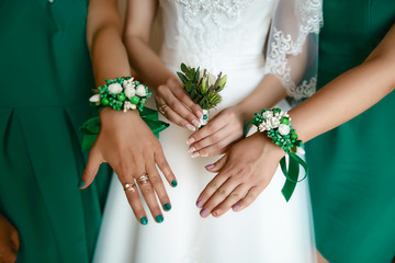 Beautiful wedding bottle with green and white flowers in the hands of the bride and girlfriends