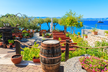 BOL TOWN, BRAC ISLAND - SEP 14, 2017: Traditional restaurant decorated with flowers and wine barrels with sea view in Bol town, Brac island, Croatia.