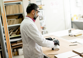 Handsome mature engineer testing colors on wooden specimens