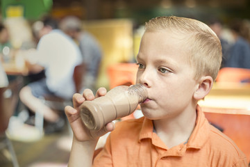 Boy drinking chocolate milk during lunch at his school cafeteria