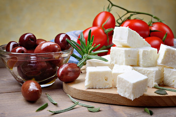 Feta cheese with kalamata olives, tomatoes and rosemary on wooden background