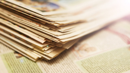 Lots of newspapers. Folded and stacked on top of each other. Selective focus