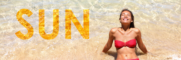 Wall Mural - Sun travel vacation in the tropical Caribbean woman sun tanning with the word SUN written on the sand texture background for advertisement concept. Banner panorama crop.