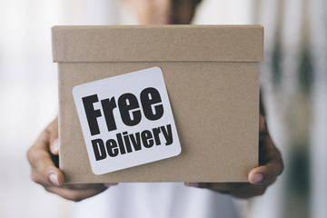 "free delivery concept - boy holding brown box with "" free delivery "" note"