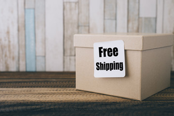 """free shipping concept - brown box with note """" free shipping """" on a wooden table"""
