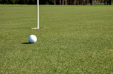Golf ball and flag on Lush green grass