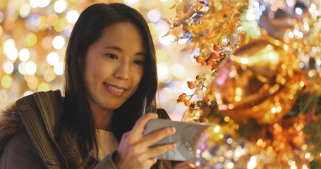 Woman taking photo on cellphone on Christmas tree decoration at night