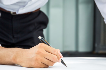 Business man writing on a big paper with his pen close up.
