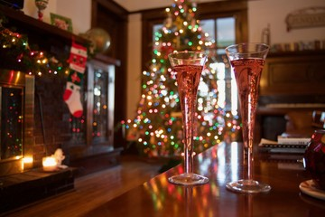 Champagne flutes in front of a decorated tree