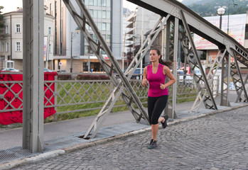 woman jogging across the bridge at sunny morning