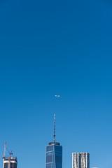 青空を飛ぶ飛行機とニューヨーク・マンハッタンの高層ビル