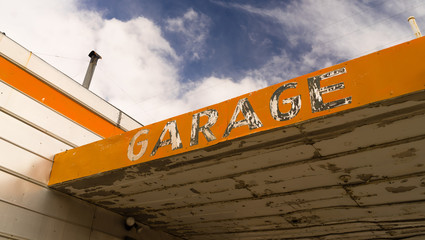Old Abandoned Garage Building Overhang Orange Sign