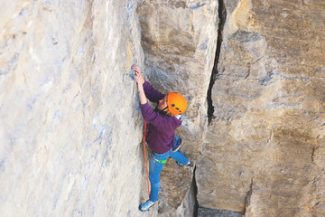 The woman in the helmet climbs the rock.