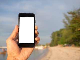 Closeup image of hand is holding black cell phone with white blank screen on the beach background