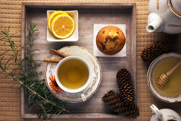 Winter tea time. Lovely arranged cup of tea next to tea ingredients,  on top of the wooden tray.