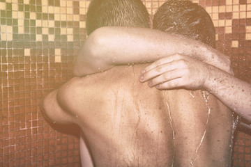 Love and relationships. Two guys are washing in the shower.