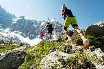 Three trail runners, two men and a woman, running up a steep trail in the mountains in the Alps on a hot, bright summer day.
