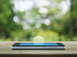Camera icon on modern smart phone screen on wooden table over blur green tree in park, Camera online shop concept