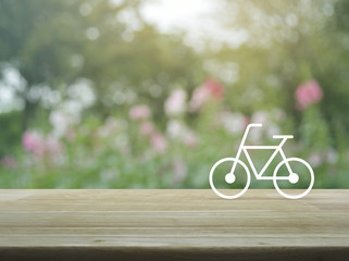 Bicycle flat icon on wooden table over blur pink flower and tree, Healthy lifestyle concept