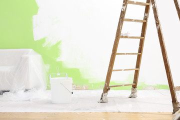 painter house concept, wooden ladder, bucket, and white and green color wall
