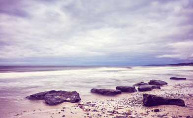 Scenic beach picture, motion blurred water, peaceful natural background, color toning applied.