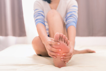 Young woman massaging her foot on the bed, Healthcare concept