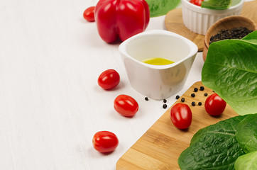 Ingredients for cooking fresh raw spring salad of green and red vegetables, spices, oil with wooden kitchenware on white wood background, border.