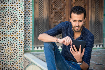 Young Muslim man working on tablet