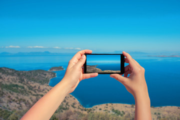 Female taking picture of landscape Greek island on mobile phone . Top view. Landscape of sea and mountain on smartphone