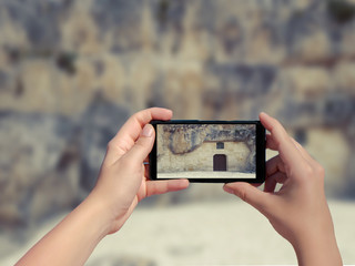 Female taking picture of old stone house in Matera in Italy on mobile phone. (sassi di Matera)