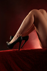 womans legs and shoes in red light