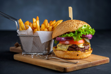 Tasty grilled beef burger with lettuce, cheese and onion served on cutting board with french fries on a black wooden table