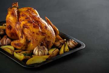 Roasted chicken with potatoes on a baking sheet.