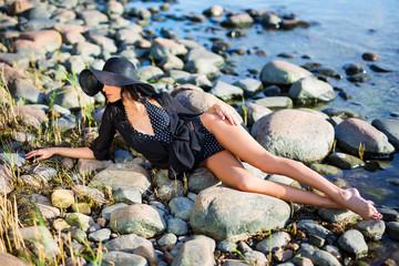 sunbathing - beautiful model in bikini lying on rocky beach