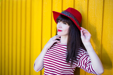 portrait of young woman in red posing over yellow wall