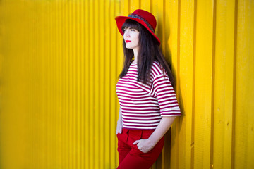 portrait of young woman in red posing over yellow wall with copy space