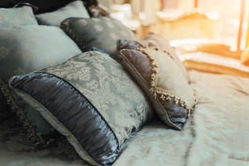 Bed maid-up with clean white  pattern pillows and bed sheets in beauty room. Close-up. Lens flair in sunlight.