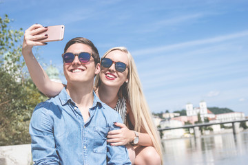 Junges Paar macht Selfie an der Innpromenade in Passau
