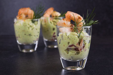 guacamole avocado cream with shrimp or prawn in a glass, appetizer or party snack on a dark slate background with copy space, close up