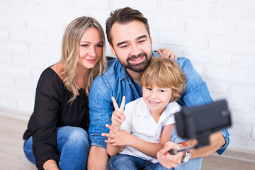 young parents and little son taking photo with smart phone on selfie stick