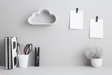 Creative desk with blank picture frame or poster, desk objects, office supplies, books and plant on a gray background. Creative desk. Wall mural