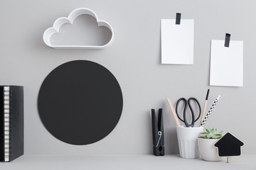 Creative desk with blank picture frame or poster, desk objects, office supplies, books and plant on a gray background. Mock up.