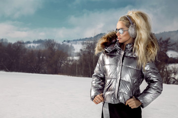 Beautiful young woman in winter, ski clothing on a background of mountains. Beautiful winter view.
