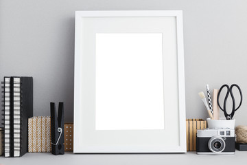 White frame mock up on a desk with books and stationery.