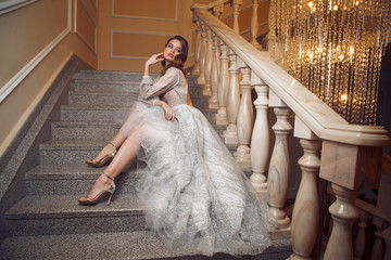 Full lenght portrait of gorgeous woman in the long silver dress on stairs