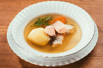 Hot soup with salmon and vegetables served in white plate on wooden table