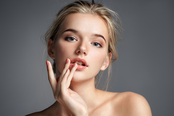 Image with beautiful blonde girl touching her lips on grey background. Beauty & Skin care concept Wall mural